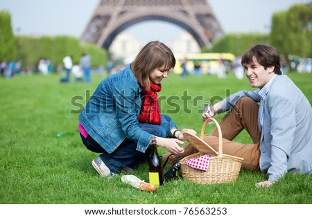 Young couple having a picnic near the Eiffel tower