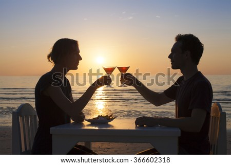 Young couple having a romantic diner on a tropical beach with two cocktails
