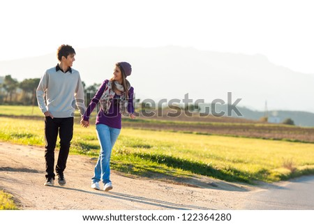 Young couple having a walk on dirt road in countryside - stock photo