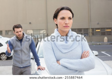 Young couple having an argument outside their car - stock photo