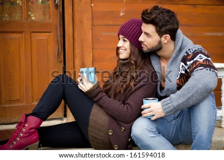 Young couple having breakfast in a romantic cabin outdoors in winter. - stock photo