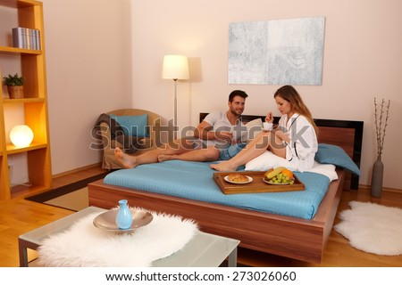 Young couple having breakfast in bed in the morning. - stock photo