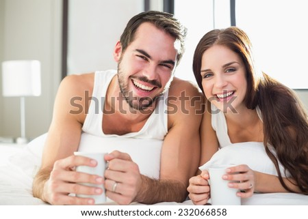 Young couple having coffee in bed at home in bedroom - stock photo