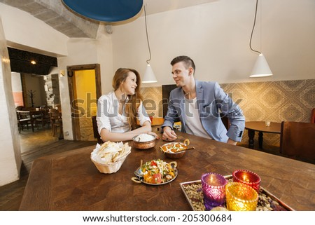 Young couple having food at restaurant - stock photo