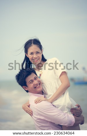 young couple having fun at tropical beach, process color