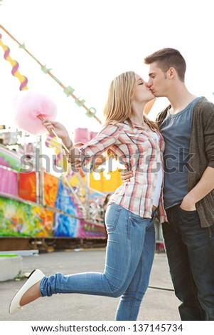 Young couple having fun in a colorful attractions park arcade, holding cotton candy and kissing spontaneously. - stock photo