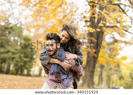 Young couple having fun in the autumn forest - stock photo