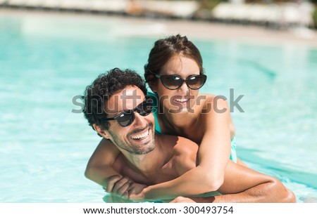 Young couple having fun in the water - stock photo