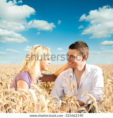 Young couple having fun in the wheat field. - stock photo