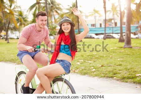Young Couple Having Fun On Bicycle Ride - stock photo