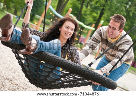 Young couple having fun - outdoors on children playground - stock photo