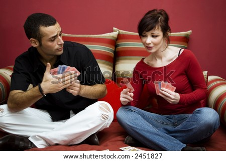 young couple having fun playing cards at home