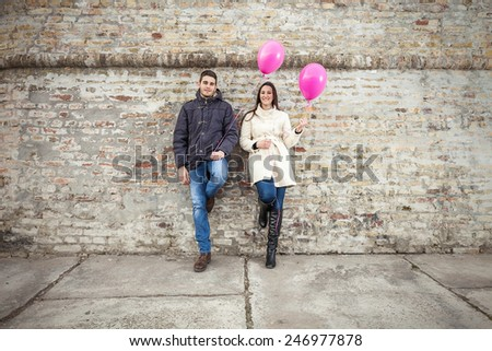 Young couple having fun playing with balloons - stock photo