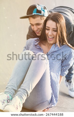 Young couple having fun skateboarding in a skate park - stock photo