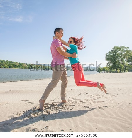 Young couple having fun spinning around on a nice sunny day on the beach - stock photo