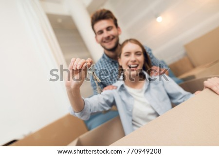 Young couple having fun while moving to new apartment. Moving newlyweds to new housing. The girl is sitting in a box and the guy is rolling her around the apartment.