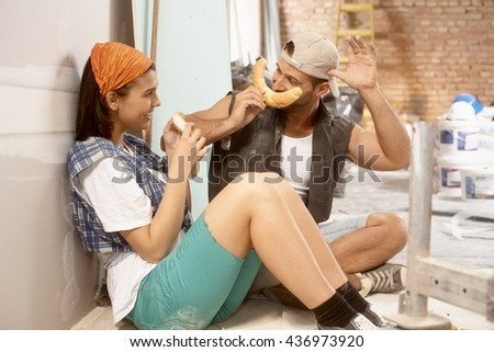 Young couple having fun with crescent rolls at home renovation. - stock photo