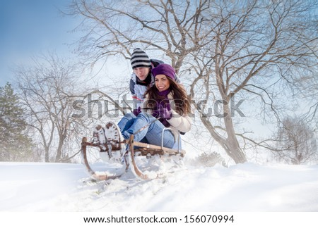 young couple having fun with sleigh outdoor, winter season  - stock photo