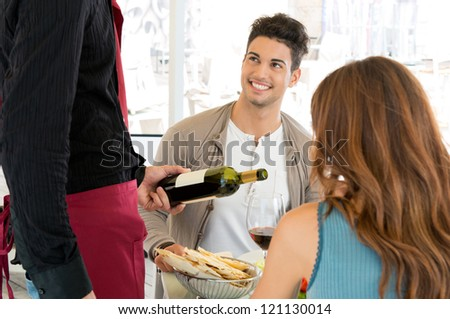 Young Couple Having Meal At Restaurant And Waiter Serving Wine
