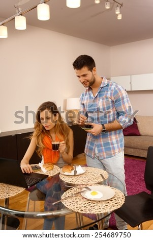 Young couple having morning coffee, using laptop computer at home. - stock photo