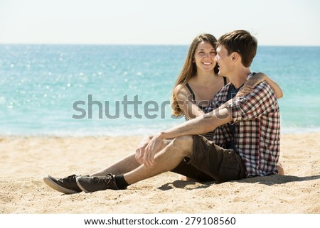 Young couple having romantic date on sunny beach - stock photo
