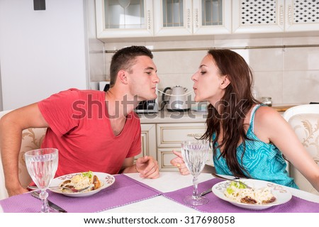 Young Couple Having Romantic Dinner Together at Home - Man and Woman Sharing Single Spaghetti Noodle Getting Closer to Kissing - stock photo