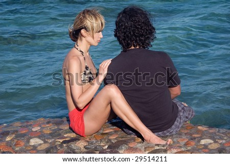 Young couple having serious conversation at the beach