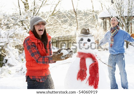 Young Couple Having Snowball Fight In Garden - stock photo
