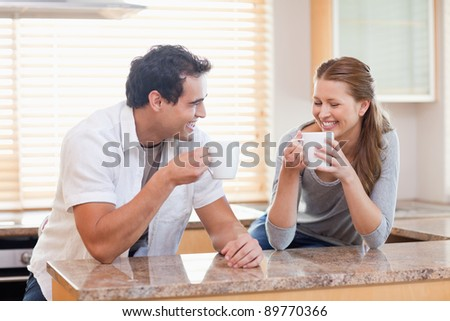 Young couple having some coffee in the kitchen - stock photo