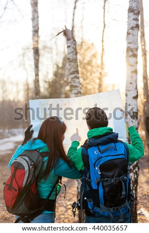 Young couple hikers looking at map.