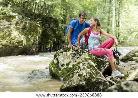 Young couple hiking in the forest - stock photo