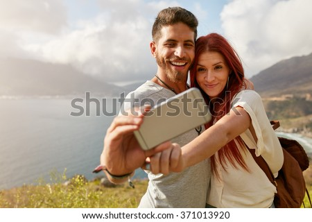 Young couple hiking taking selfie with smart phone. Happy young man and woman taking self portrait with mountain scenery in background. - stock photo