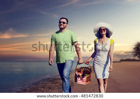 Young couple holding a basket walking on the seaside in the evening