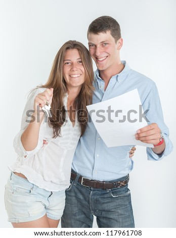 Young couple holding a document and a bunch of keys - stock photo