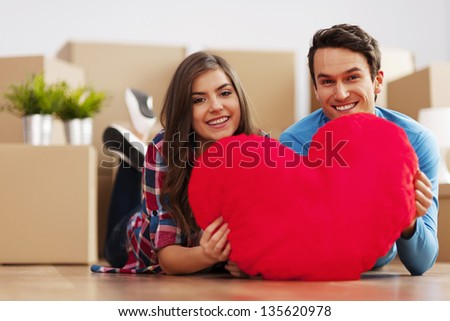 Young couple holding a heart shape pillow - stock photo