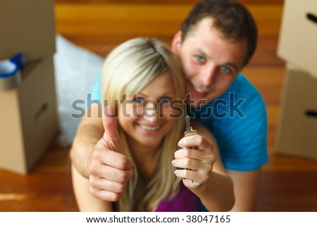 Young couple holding a key with thumbs up. Buying new house