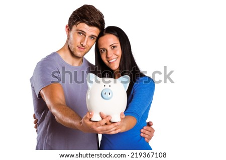 Young couple holding a piggy bank on white background - stock photo