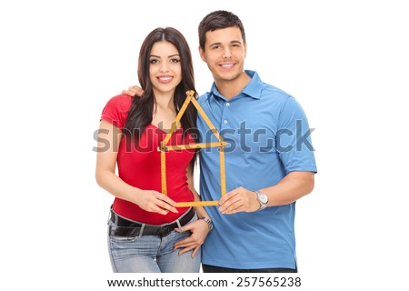 Young couple holding a tape measure in the form of a house isolated on white background - stock photo