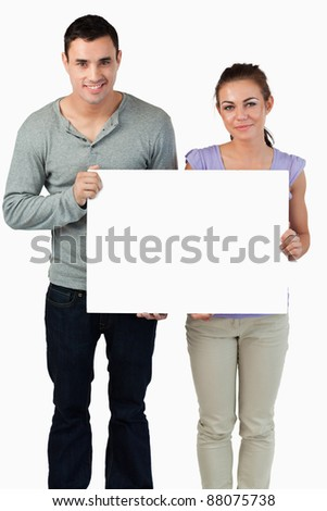 Young couple holding banner together against a white background