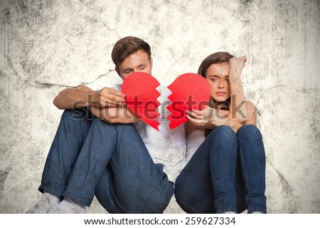 Young couple holding broken heart against grey background - stock photo