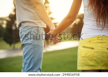 Young couple holding each other's hands. Man in blue jeans and woman in yellow skirt in love isolated on sunset. - stock photo