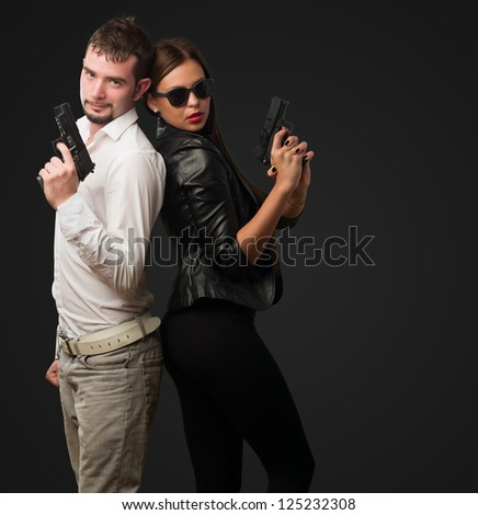 Young Couple Holding Gun against a black background - stock photo