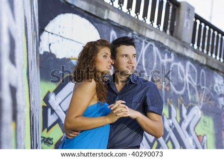 Young couple holding hands against graffiti wall.