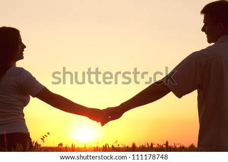 Young couple holding hands and looking at each other on sunny summer day. - stock photo