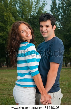 Young couple holding hands and smiling in park - stock photo