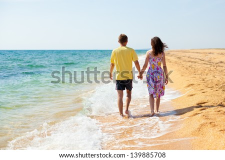Young couple holding hands and walking carefree on the beach on summer vacation - stock photo