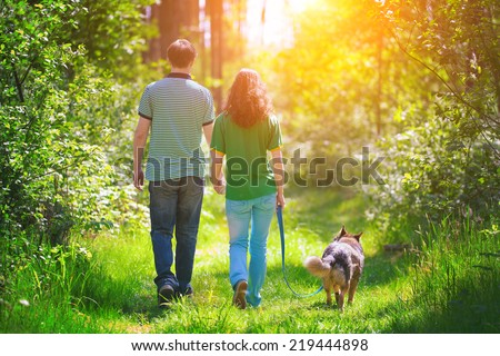 Young couple holding hands and walking with their dog in the forest - stock photo