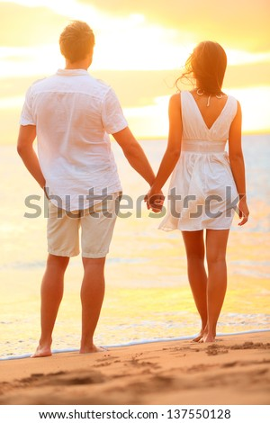 Young couple holding hands at beach sunset enjoying romance and sun. Young happy couple in love on romantic summer holidays vacation. Young lovers in casual clothing. Asia woman, Caucasian man. - stock photo