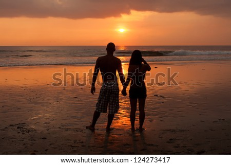 Young couple holding hands at sunset on beach