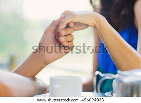 young couple holding hands having date at cafe